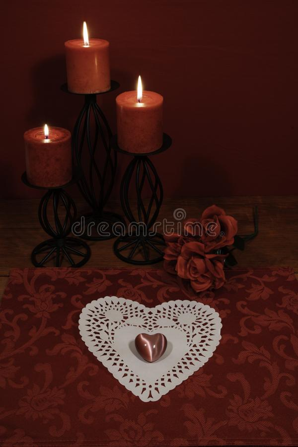 Heart shaped dollie and gemstone, three red candles in metal holders and bouquet of red roses on wooden table. stock photography