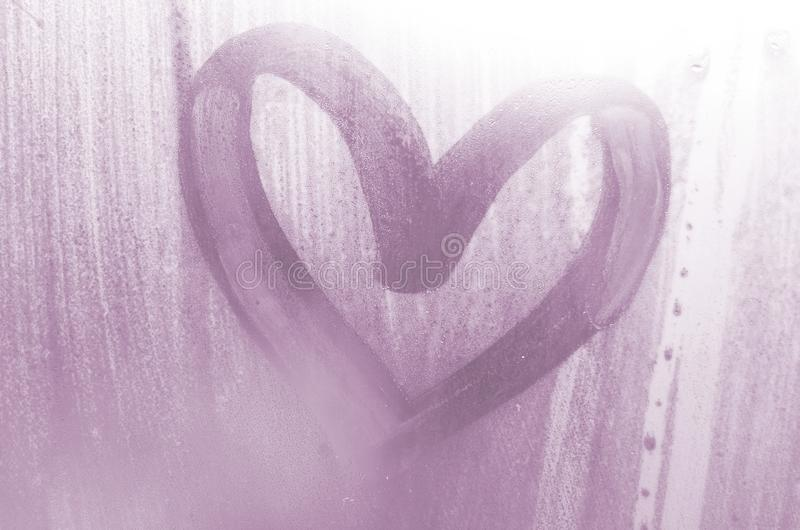 A heart-shaped drawing drawn by a finger on a misted glass in rainy weather.  stock photos
