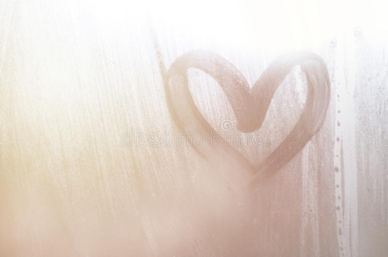 A heart-shaped drawing drawn by a finger on a misted glass in rainy weather.  royalty free stock photography