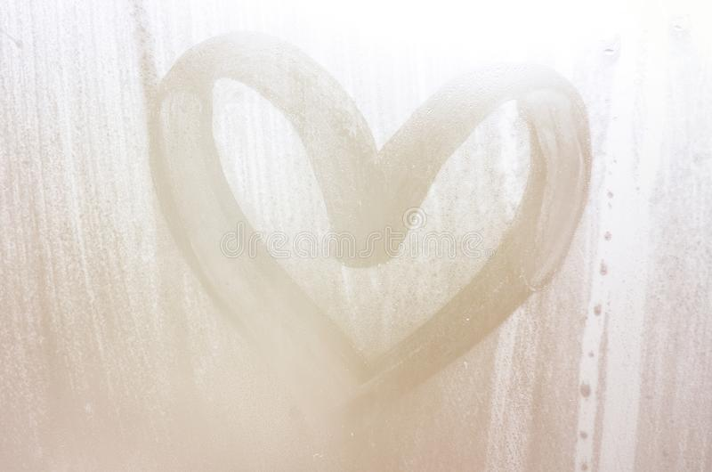 A heart-shaped drawing drawn by a finger on a misted glass in rainy weather.  stock photo