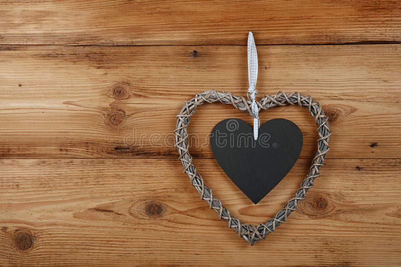 Heart shaped frame with blackboard on wooden wall. Heart shaped handmade wicker braided frame with chalk blackboard copy space on old vintage rustic brown wooden royalty free stock image