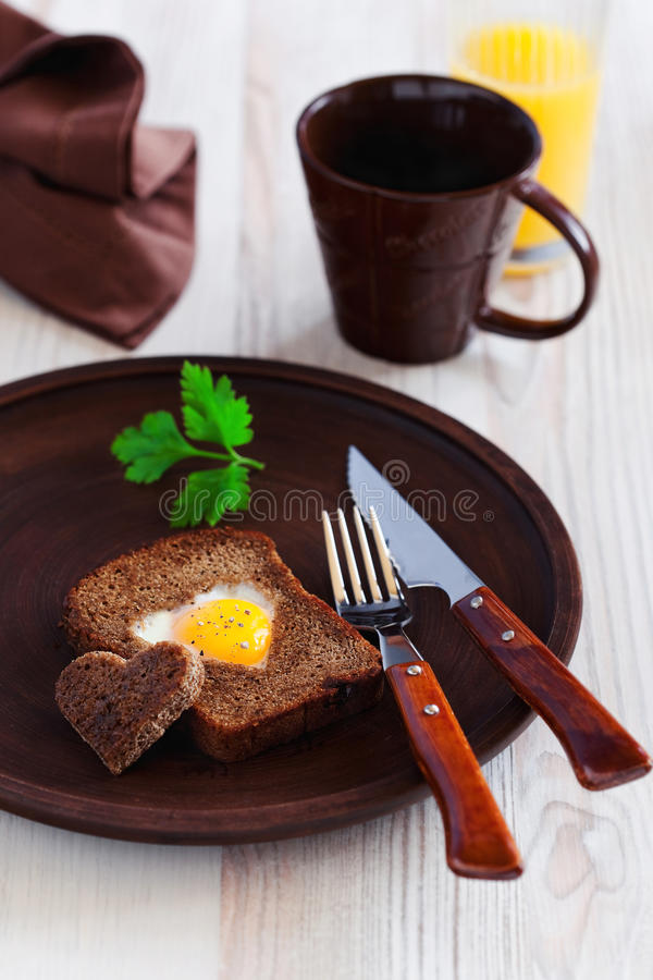 Heart shaped fried egg in toast. Of black bread, selective focus royalty free stock images