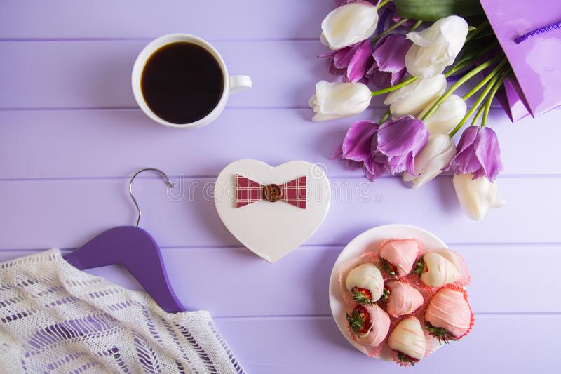 Heart shaped gift box, bouquet of purple and white tulips, cup of coffee, strawberry in chocolate and hanger with clothes on lilac. Wooden background. Spring royalty free stock photos
