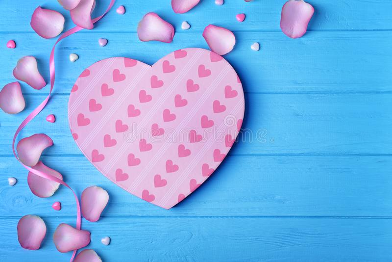 Heart shaped gift box and petals on blue wooden background royalty free stock images