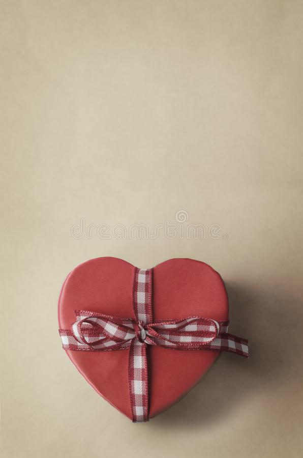 Heart Shaped Gift Box with Gingham Checked Ribbon. A heart shaped, undersaturated, warm pink gift box with gingham checked ribbon bow on a cream parchment style royalty free stock image