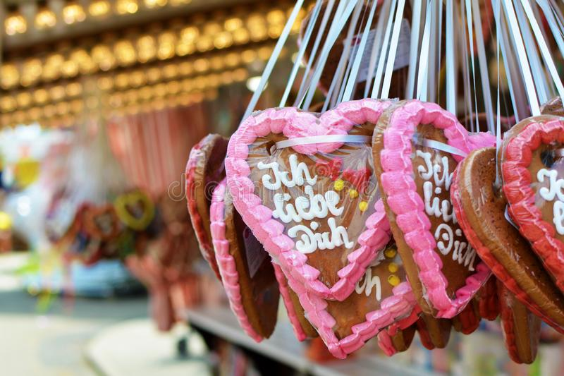 Heart shaped gingerbread candy decorated with colorful sugar icing and `I love you` written in German on them royalty free stock photography
