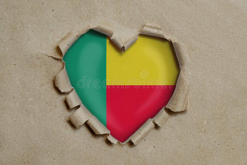 Heart shaped hole torn through paper, showing Benin flag stock images
