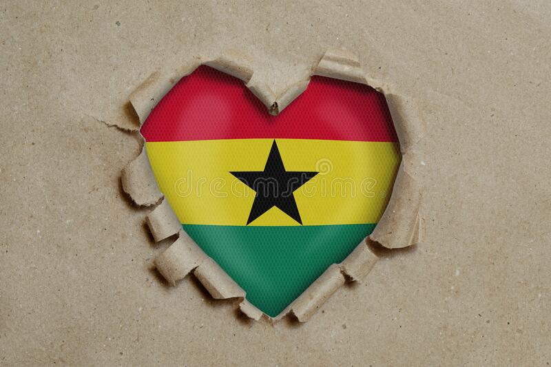 Heart shaped hole torn through paper, showing Ghana flag stock image