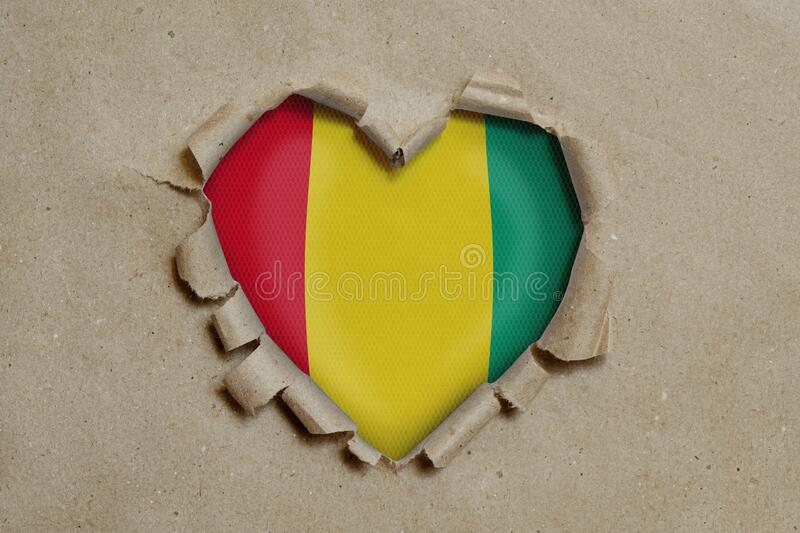 Heart shaped hole torn through paper, showing Guinea flag royalty free stock photography