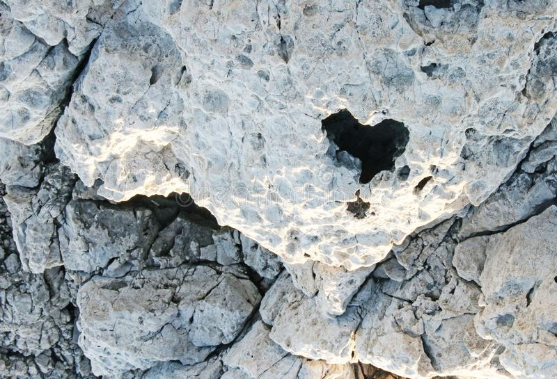 Heart shaped hole in a white stone textured wall. Background, abstract, beautiful, black, cement, concept, concrete, crack, day, decor, design, house, life stock photo