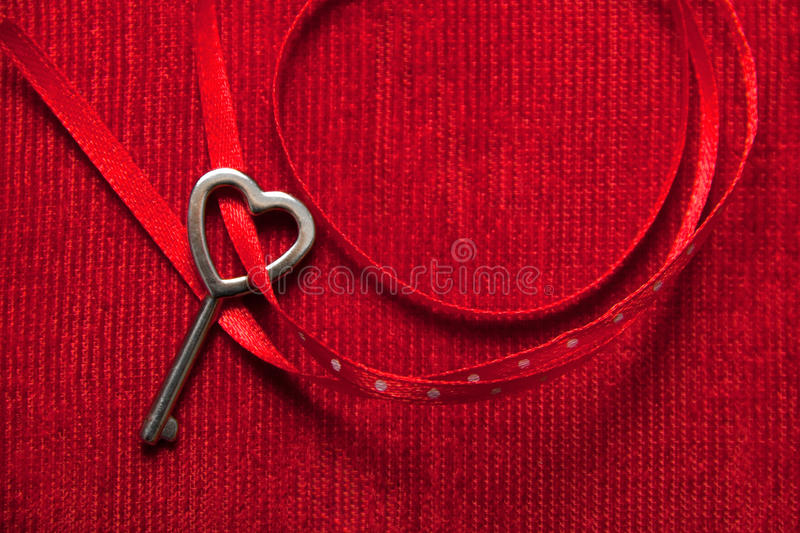 Heart shaped key and red ribbon on velvet royalty free stock images
