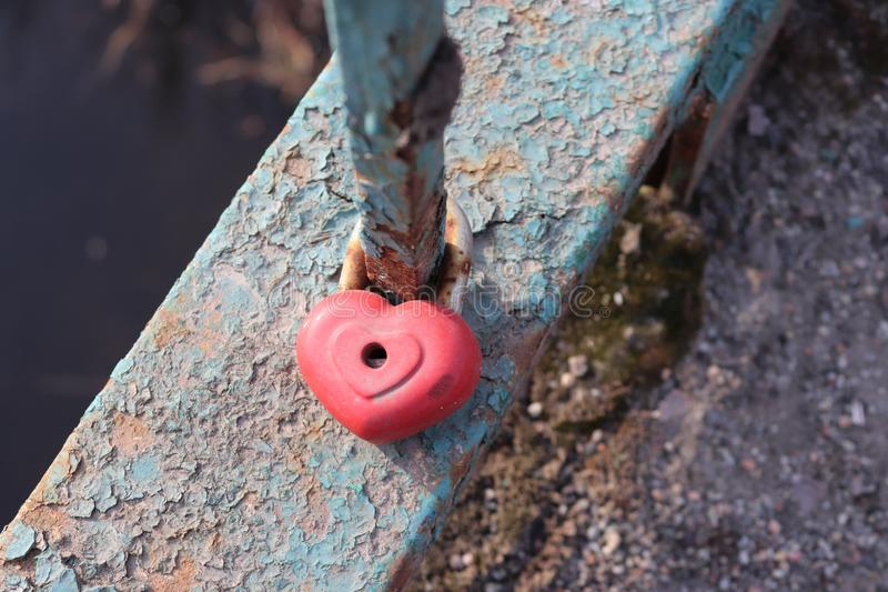 Heart shaped lock. Red colored snap on the bridge. Traditions of lovers. Wedding symbols stock photo