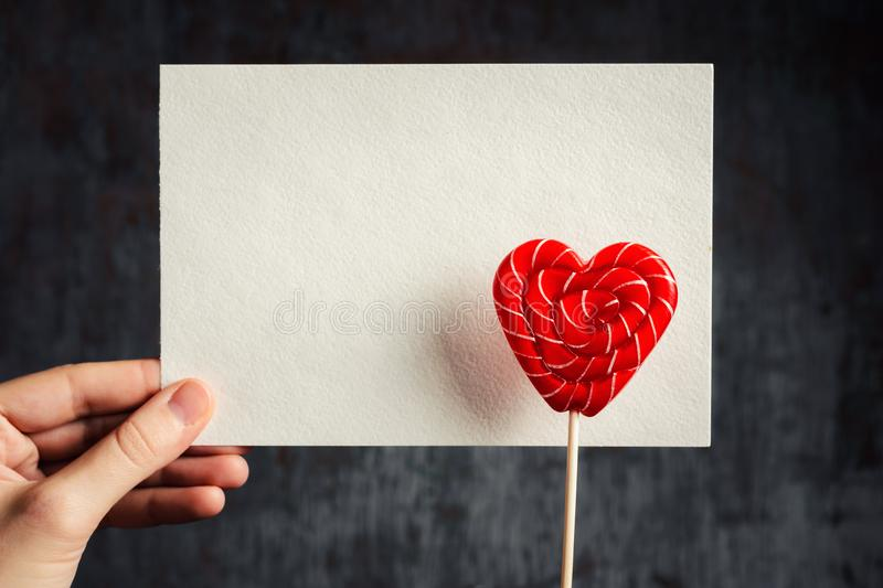 Heart shaped lollipop with white empty sheet in woman hand on a dark background. Mockup for Valentines Day royalty free stock photo