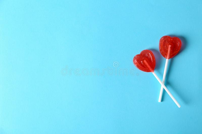 Heart shaped lollipops and space text color background. Top view. Sweet love royalty free stock image