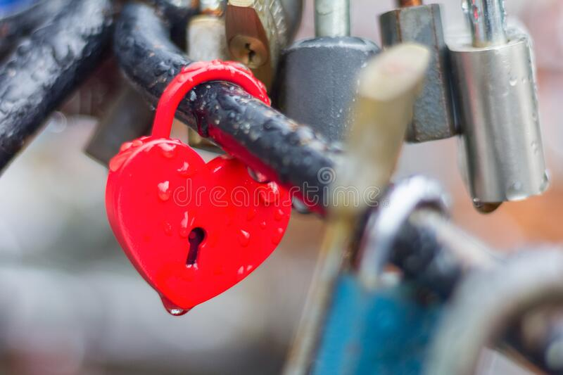 Heart-shaped love padlock with drops of rain stock images