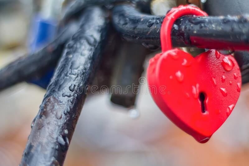 Heart-shaped love padlock with drops of rain royalty free stock image