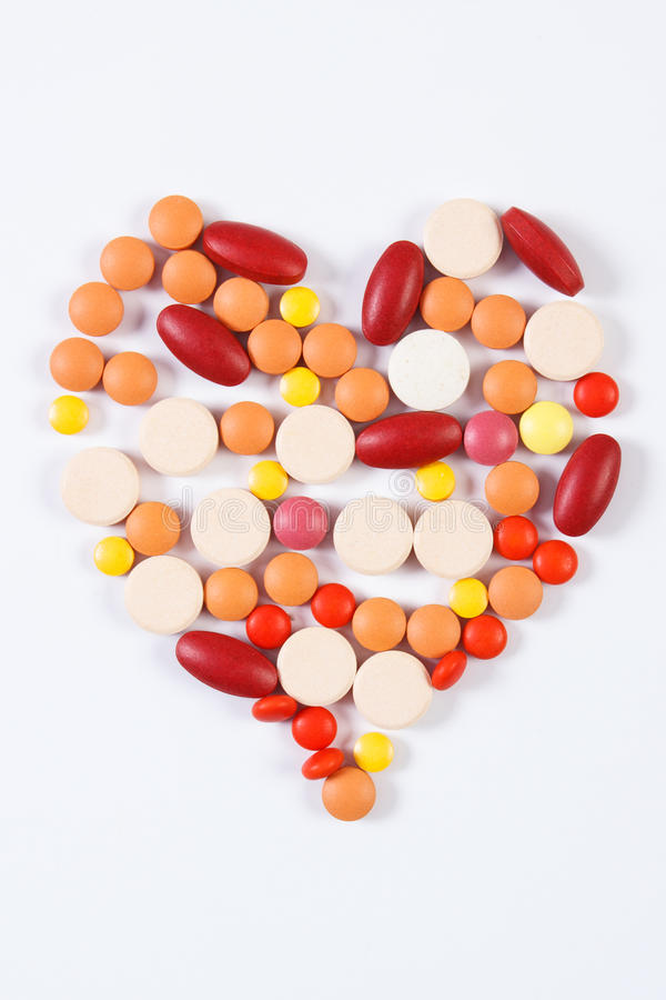 Heart shaped medical pills and capsules on white background, health care concept stock photo
