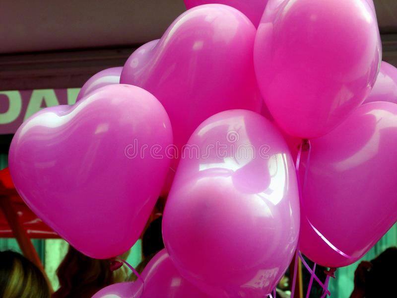 heart shaped pink balloons on strings with blurry background stock photography