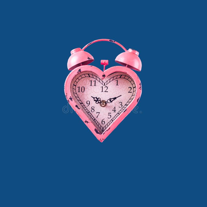 Heart shaped pink clock on classic blue background. Valentines day and love infitity and duration concept. Square stock photos