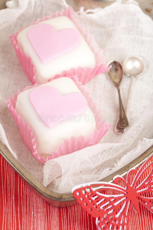 Heart shaped pink cupcakes in tin tray. With spoons , red background royalty free stock photo