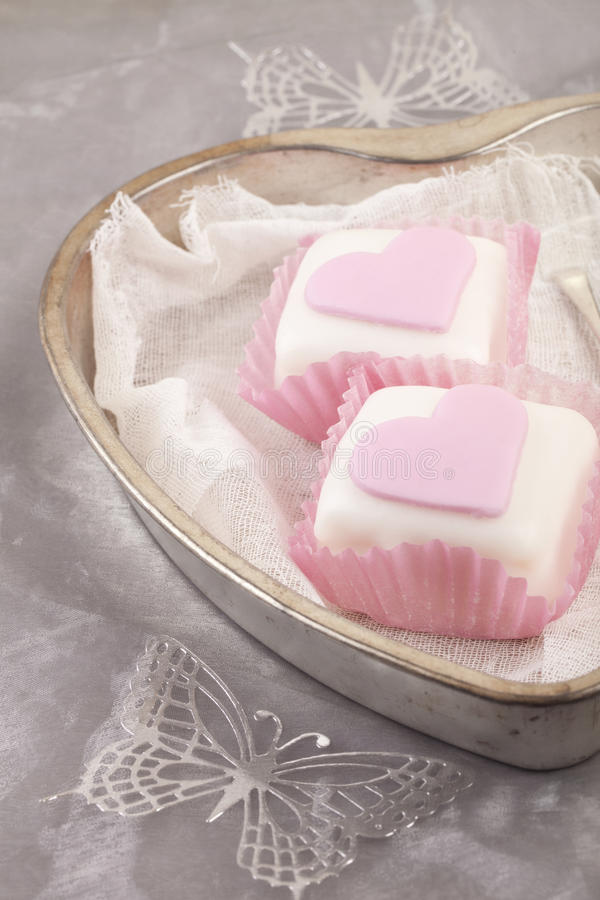Heart shaped pink cupcakes in tin tray. With gray shine background stock images