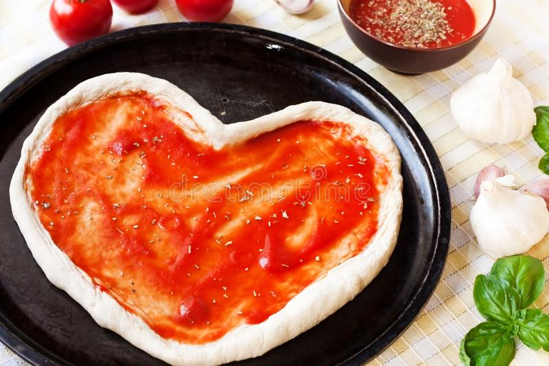 Heart-shaped pizza dough with tomato sauce royalty free stock photos