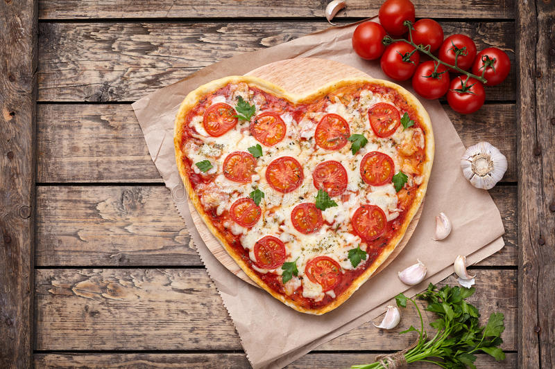 Heart shaped pizza margherita vegetarian love concept with mozzarella, tomatoes, parsley and garlic composition on stock photo