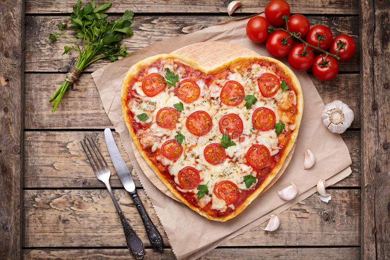 Heart shaped pizza margherita vegetarian love concept with mozzarella, tomatoes, parsley, knife, fork and garlic stock images