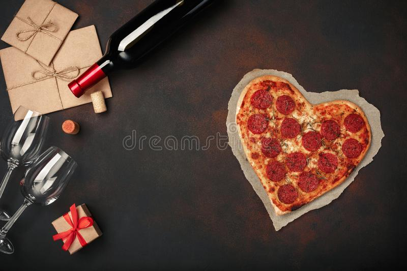 Heart shaped pizza with mozzarella, sausagered, wine bottle, two wineglass, gift box on rusty background. Top view stock image