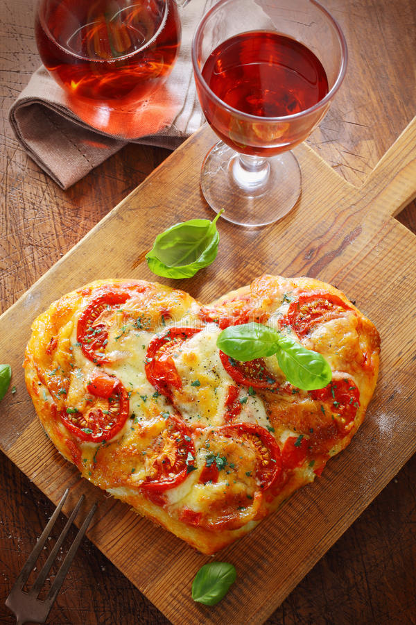 Heart shaped pizza with red wine royalty free stock images