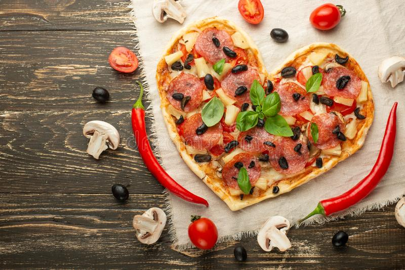 Heart-shaped pizza, Valentine`s Day. With vegetables. A concept of tasty and healthy food with love. Free-lay royalty free stock photos