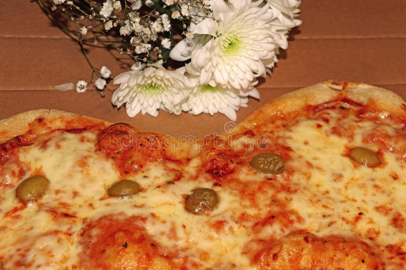 Heart-shaped pizza and white chrysanthemum flowers. For Valentine`s Day royalty free stock photography
