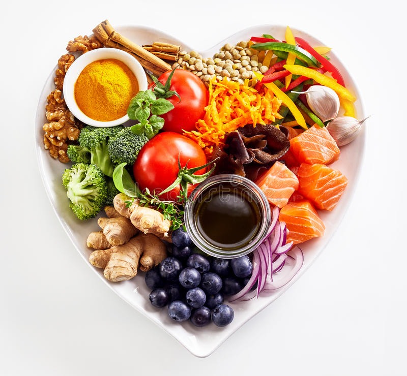 Heart-shaped plate of healthy heart foods. With acai, lentils, soy sauce, ginger, salmon, carrot, tomato, turmeric, cinnamon, walnuts, garlic, peppers, broccoli stock photos