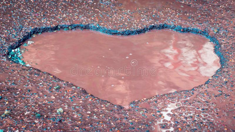 Heart Shaped Pothole In The Old Asphalt Road With Puddles, Gravel, Stones. Love Sign. Heart Shaped Pothole In The Old Asphalt Road With Puddles, Gravel, Stones royalty free stock photo