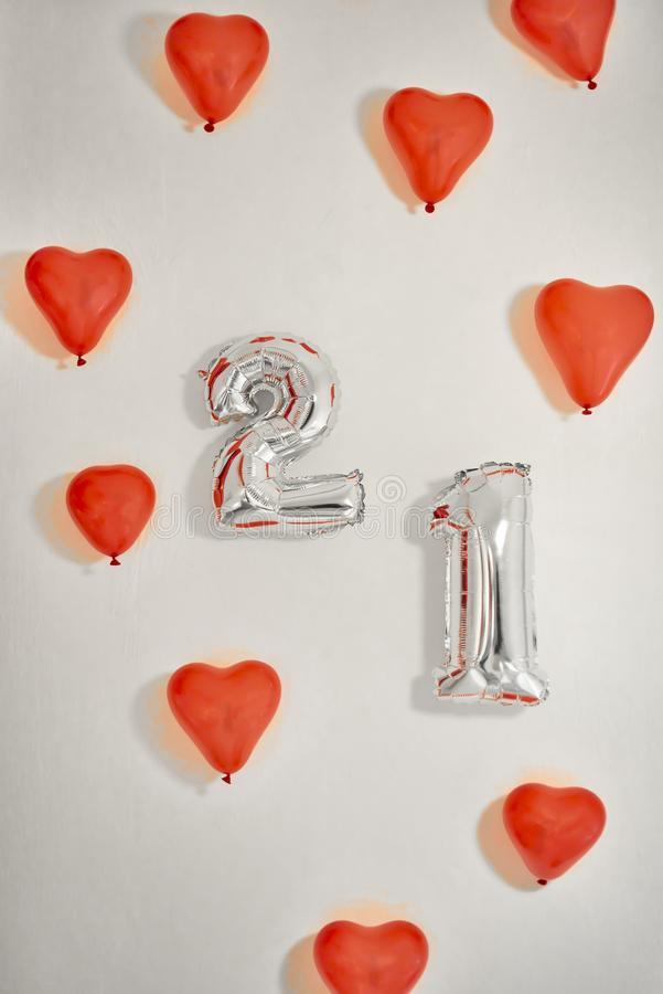 Heart shaped red balloons and number 21 balloons on white background. royalty free stock photos