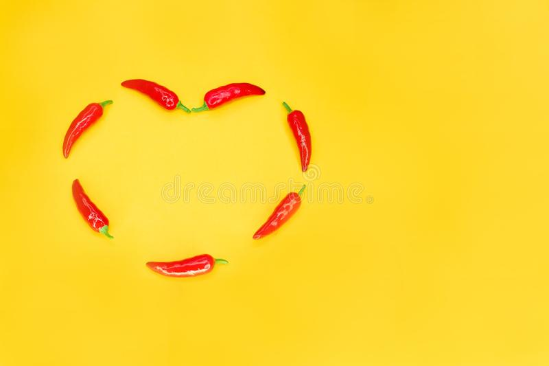 Heart shaped red chili peppers on yellow background with copy space. Passionate love concept stock photo