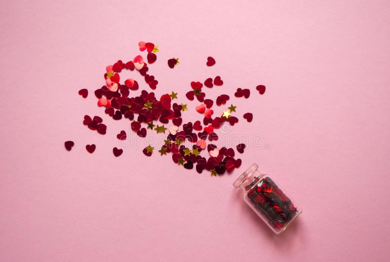 Heart shaped red color confetti on pink background in star shaped box royalty free stock photos