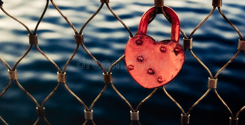 Heart-shaped red love lock hanging on a metal bridge railing stock photography