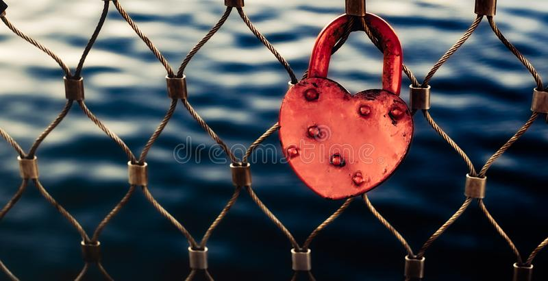 Heart-shaped red love lock hanging on a metal bridge railing stock photos