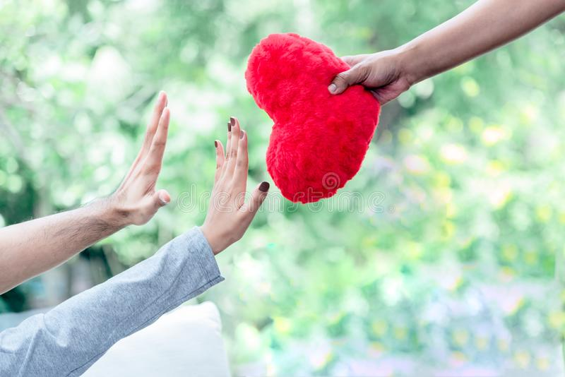 Heart shaped red pillow in the hands of people stock photos