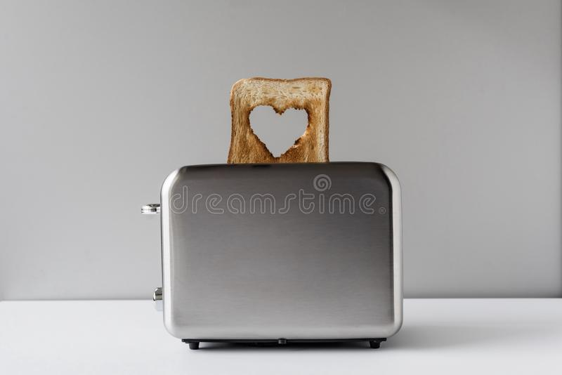 Heart shaped on roasted toasted bread in a toaster. Breakfast preparation on Valentine`s Day. symbol sign of love. Concept. Heart shaped on roasted toasted royalty free stock images