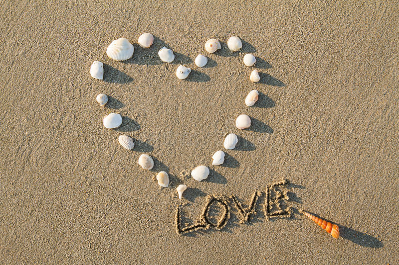 Heart shaped sea shells and drawing letter love on the sand beach royalty free stock photography