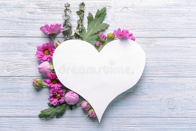 Heart shaped sheet of paper with beautiful flowers and leaves on light wooden background royalty free stock photography
