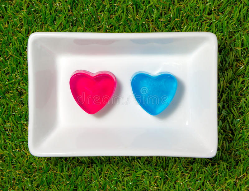 Heart-shaped soap on with dish with green grass