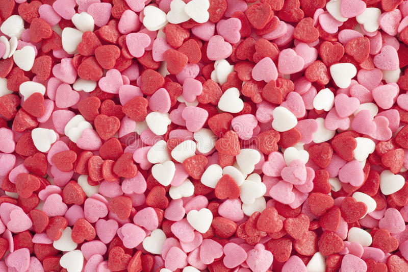 Heart shaped sprinkles background. stock photo