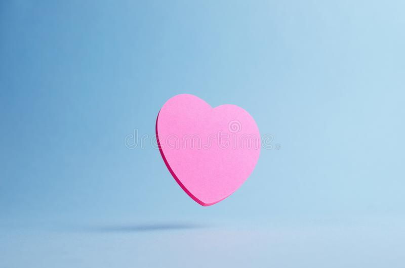 Heart shaped sticky note. Pink heart shaped sticky note falling over blue background royalty free stock photo