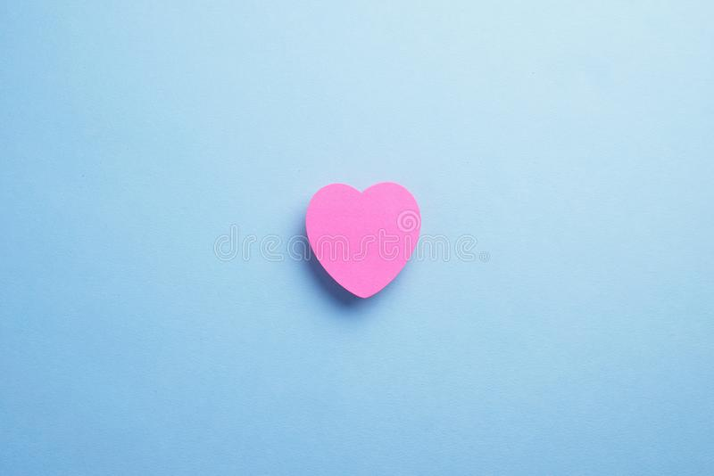 Heart shaped sticky note. Pink heart shaped sticky note over blue background, top view with negative space stock image