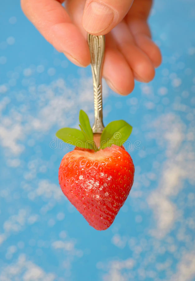 A heart shaped strawberry in spoon. And sugar on background stock photo