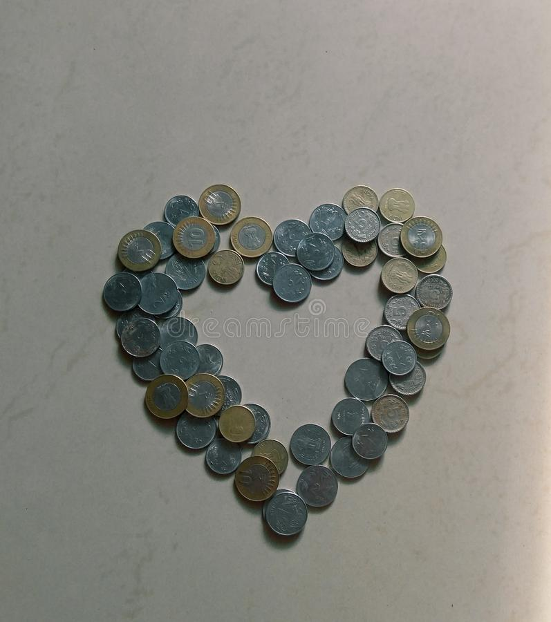 heart shaped structure made with Indian currency coins in a white marble background stock photography