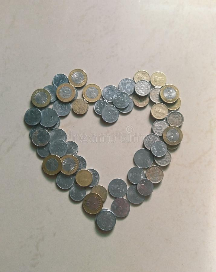 heart shaped structure made with Indian currency coins in a white marble background royalty free stock photos